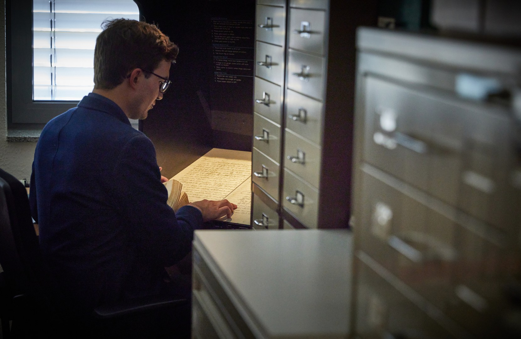 Mithilfe eines Lesegeräts vergrößert Jonas Bechtold den Inhalt eines Mikrofilms. Zu sehen ist einer der kaiserlichen Friedensverträge.