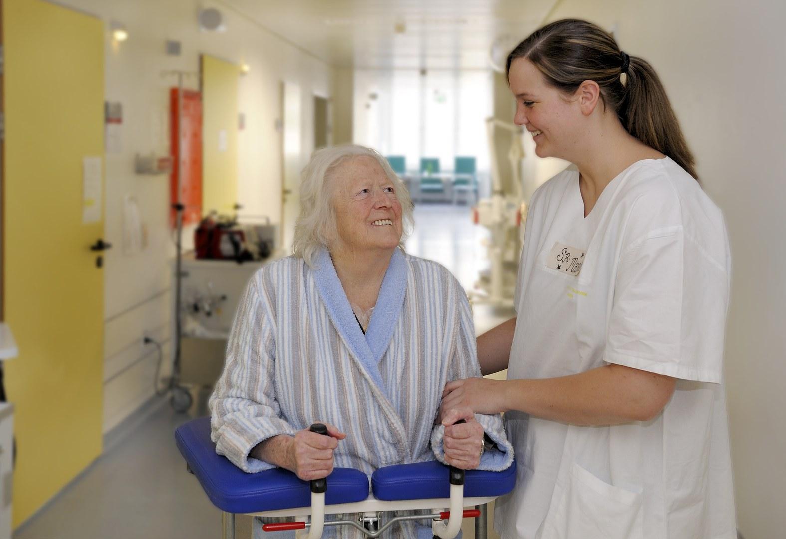 Eine Pflegeschülerin hilft einer Patientin