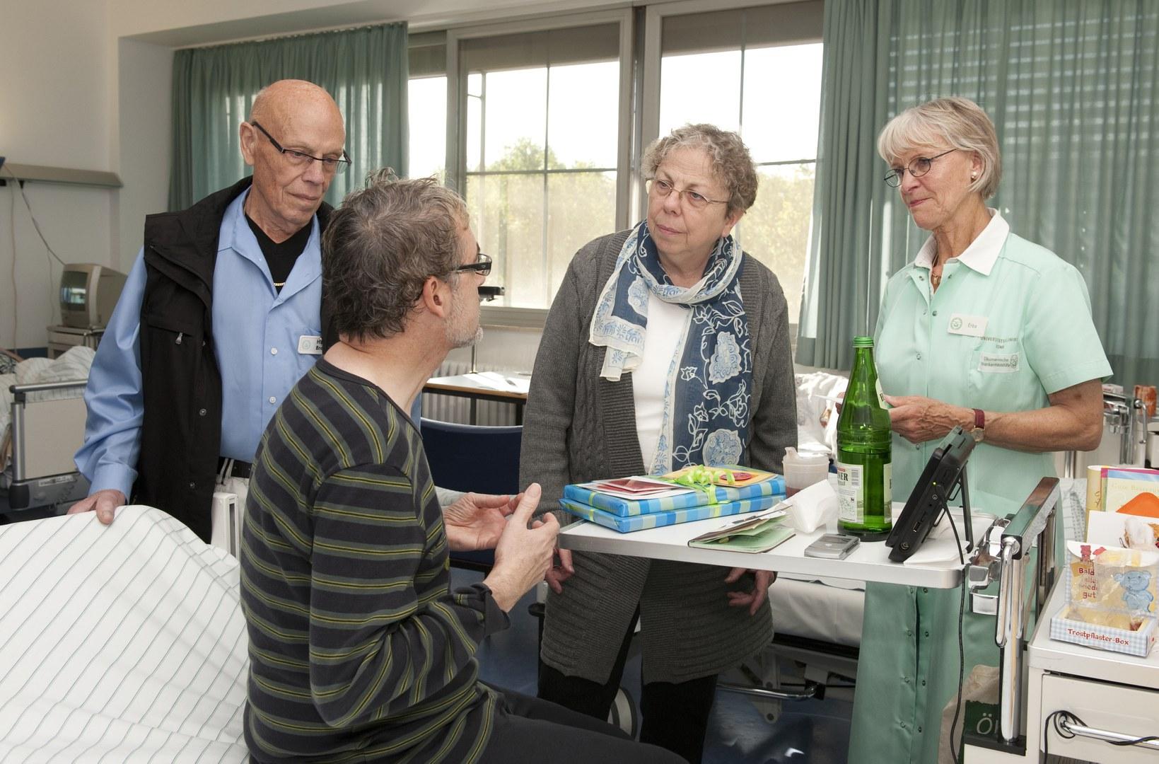 Grüne Damen und Grüner Herr im Gespräch mit einem Patienten (vorne):