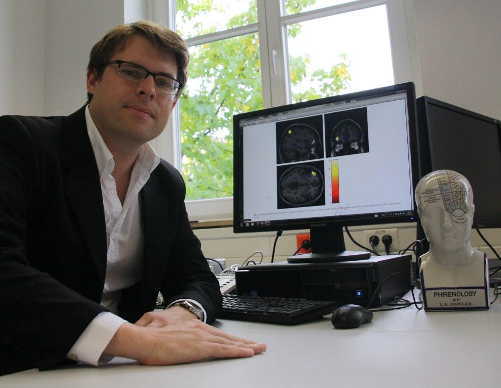 Dr. Christian Montag mit Hirnscans der Probanden: