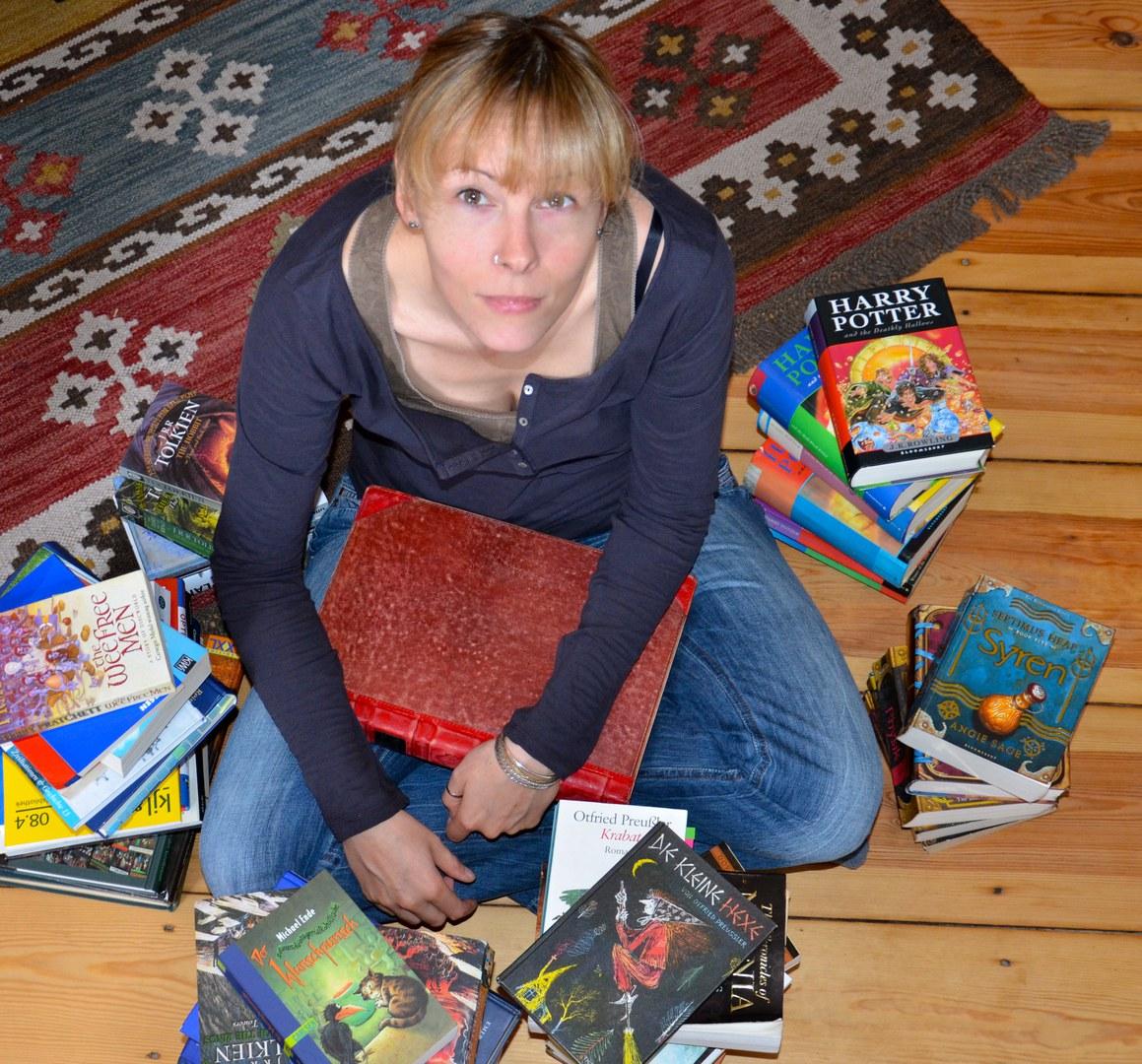 Umringt von Kinder- und Jugendbüchern:
