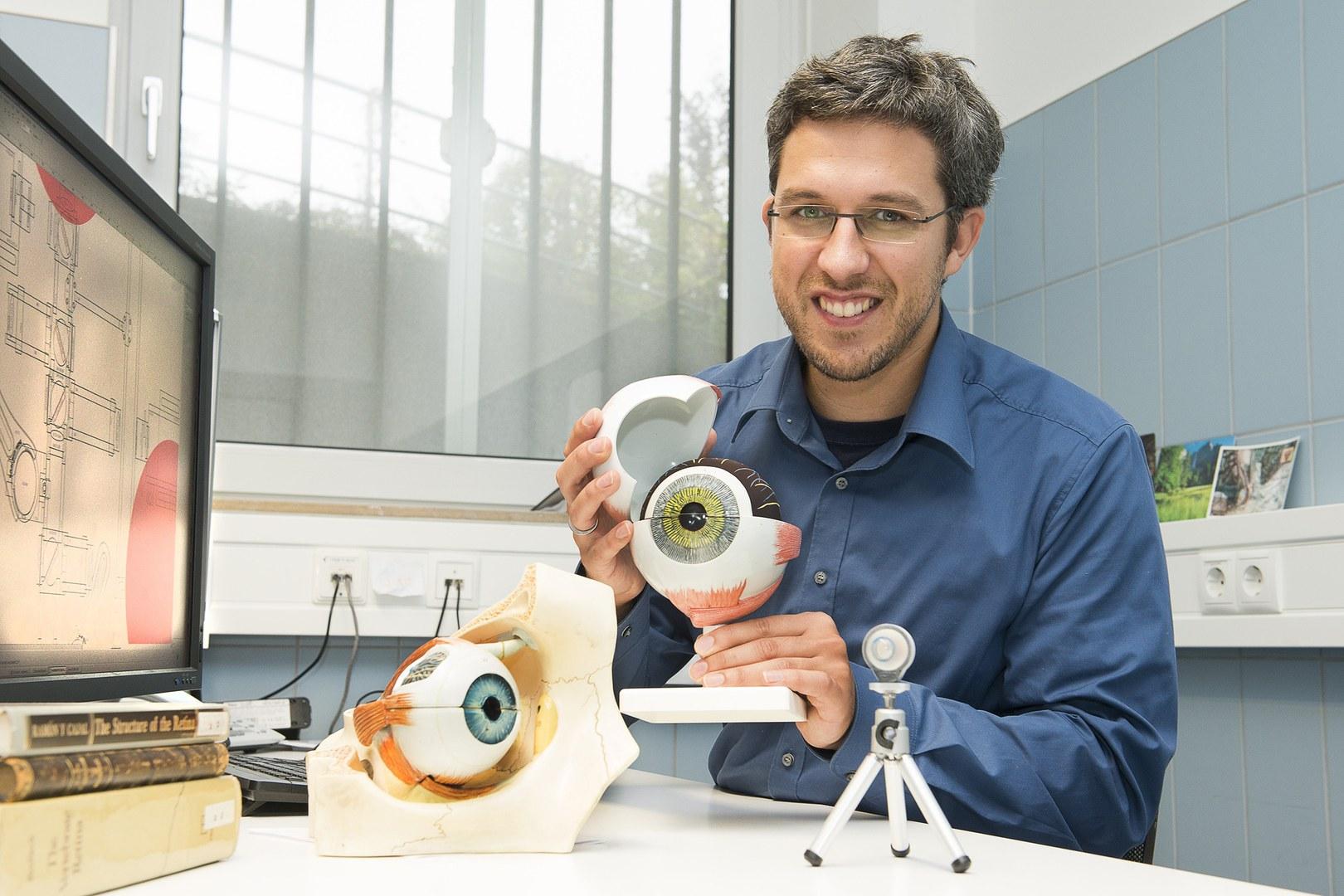 Dr. Wolf Harmening mit Modellen des menschlichen Auges: