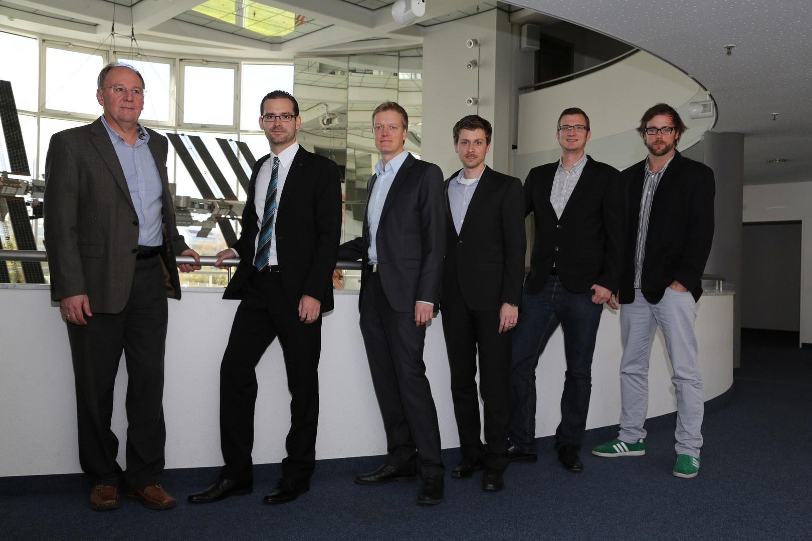 Die Projektbeteiligten vor einem Modell der ISS am Deutschen Zentrum für Luft- und Raumfahrt (DLR):