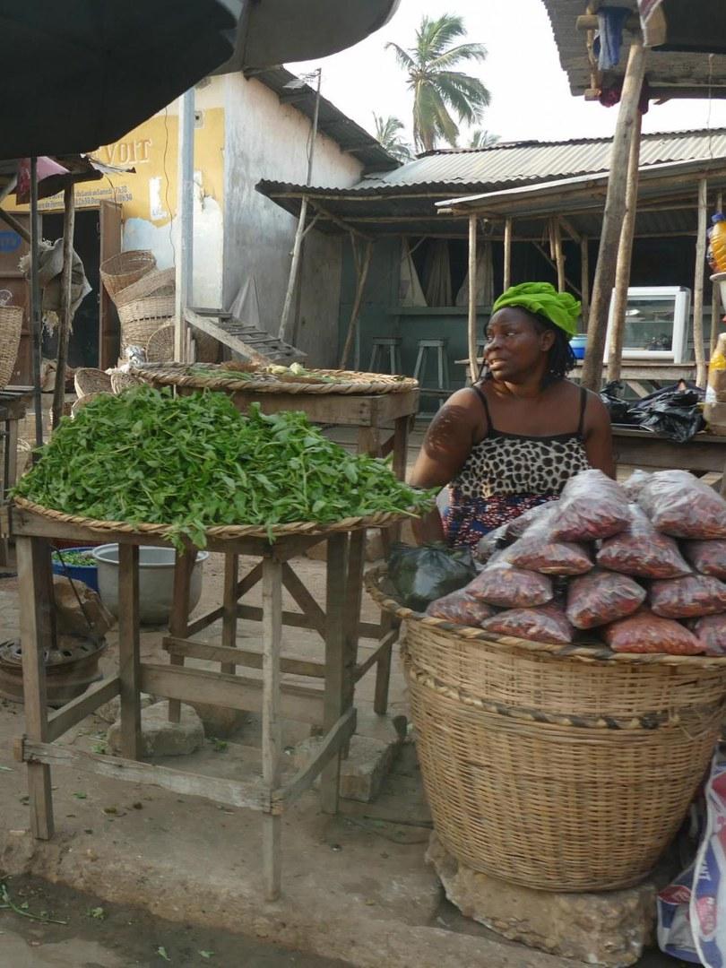 Marktfrau mit unverpacktem Blattgemüse