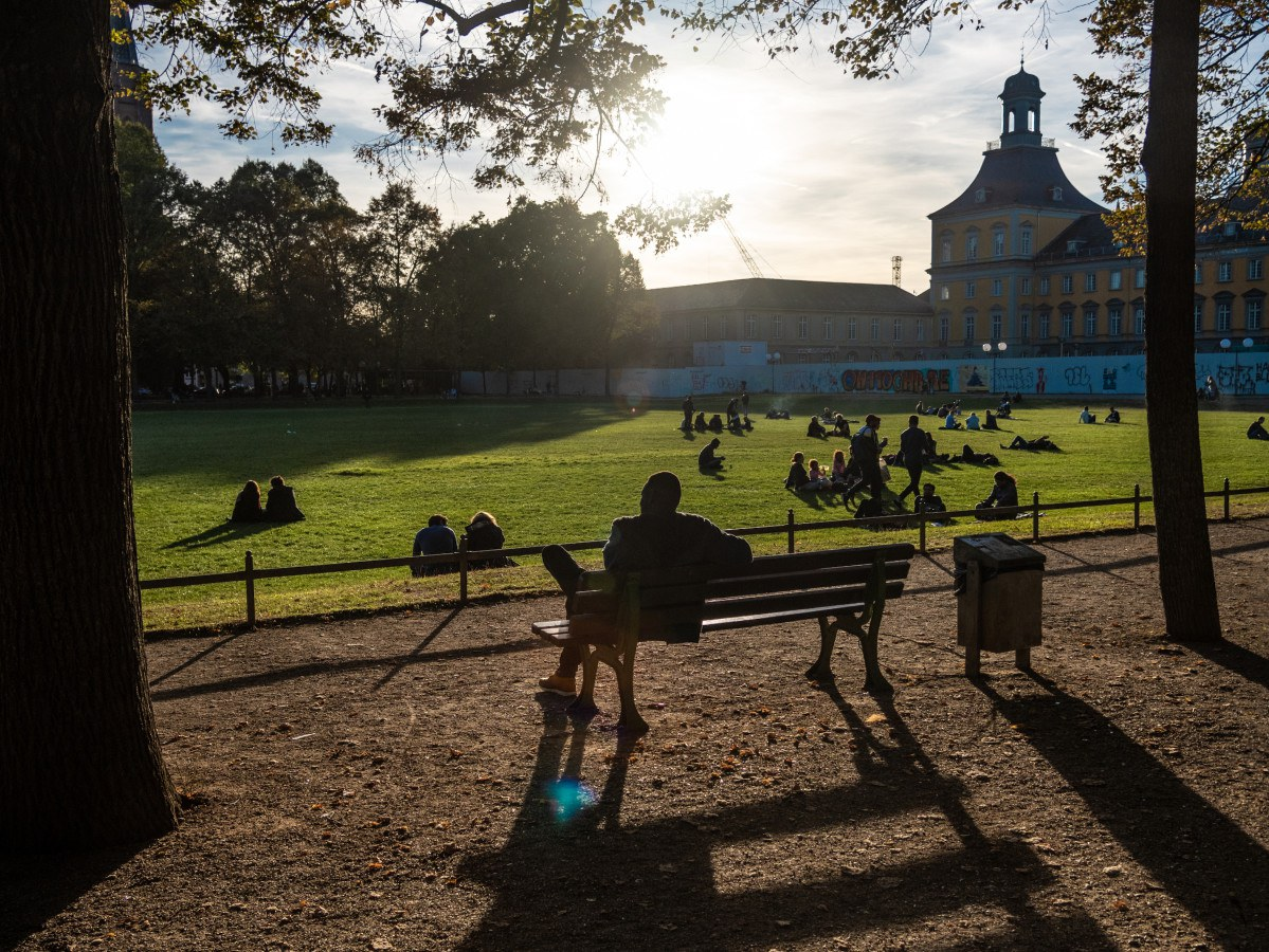 A man sits alone on a park bench in the Hofgarten.